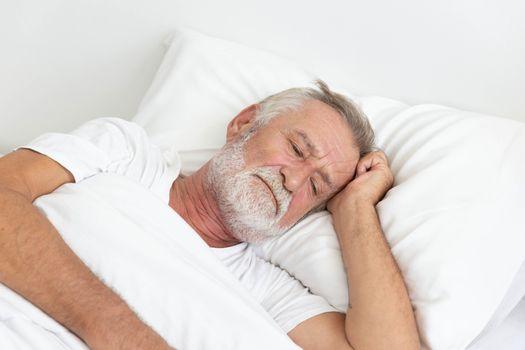 Worried senior retirement man lying awake in his bed