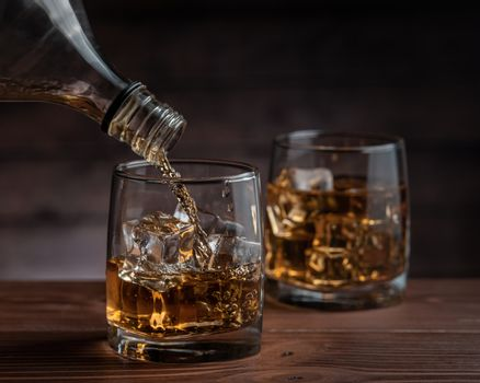 Whiskey pours from a bottle into a glass
