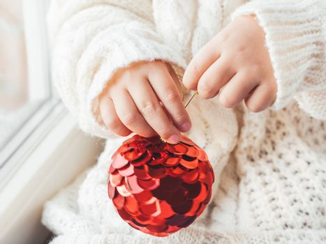 Kid with red decorative ball for Christmas tree. Boy in cable-knit oversized sweater. Cozy outfit for snuggle weather. Winter holiday spirit. New year.