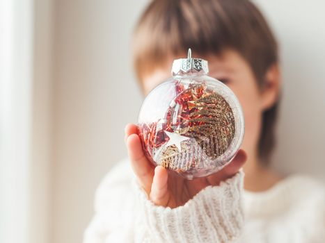 Kid with decorative ball for Christmas tree.Boy in cable-knit oversized sweater.Cozy outfit for snuggle weather.Transparent ball with red, golden spangles inside.Winter holiday spirit.New year.