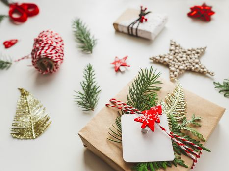Christmas DIY presents wrapped in craft paper with fir tree branches. Red decorations in shape of Christmas tree. New Year gifts. Festive background. Winter holiday spirit.