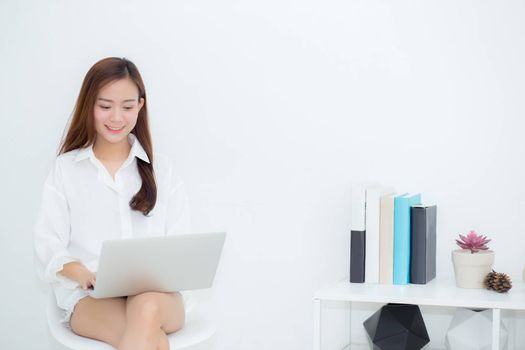 Beautiful young asian woman using laptop for leisure on sofa, girl working online with notebook freelance, communication business concept.