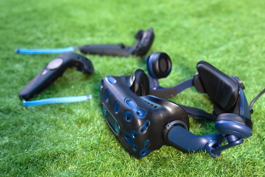 VR virtual reality headset and two controllers over green background.