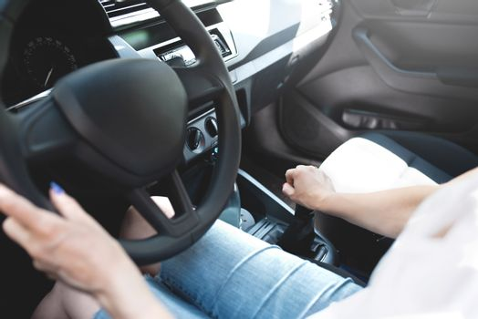 Close up woman hands keeping steering wheel while sitting in modern interior of vehicle. Girl driving car at street concept
