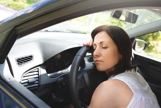 Tired woman asleep on steering wheel in her car