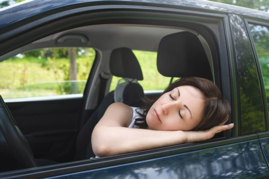 Very tired woman sleeping on a car window.driving safety concept