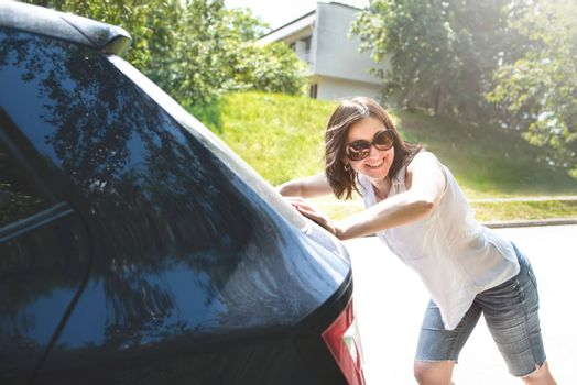 woman pushing broken car while her boyfriend is driving