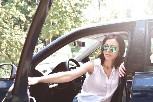 Beautiful middle-aged caucasian woman stepping out the car