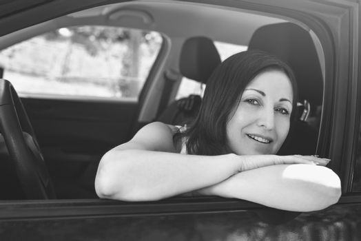 Smiling female driver looking out the car
