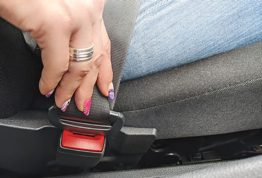 The woman's hand is fastened with a seat belt to start driving on the Car. Closeup image of a woman sitting in car and putting on her seat belt