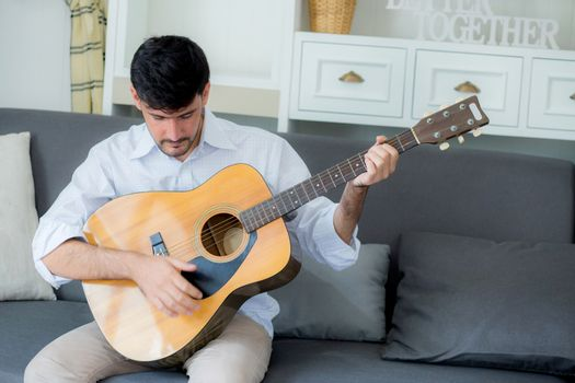 Portrait young asian man relax sitting on sofa with playing solo