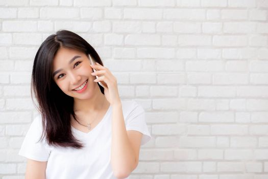 Beautiful of portrait young asian woman talk smart phone and smile standing on cement brick background, freelance female calling telephone, communication of mobile concept.