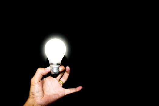 Glowing light bulb on hand on white background.