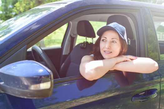 Smiling female driver in hat looking out the car. a portrait of a smiling woman sitting in the car, looking at the camera.