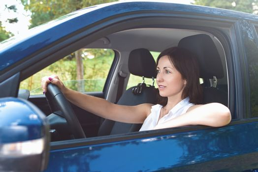 Beautiful adult happy woman driving her car in sunny summer day