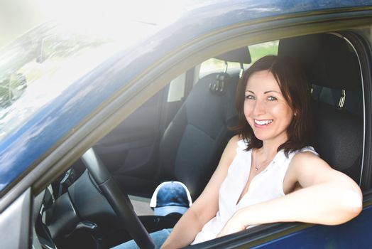 Happy adult woman driving a car and smiling. success happy brunette woman is driving a car. Portrait of happy woman driver.