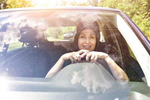Beautiful adult happy woman driving her car in summer day