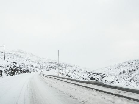 Driving through snowy road and landscape in Norway.