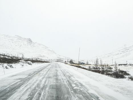 Driving through blizzard snowstorm with black ice on road, Norway.
