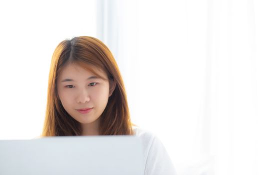 Portrait of beautiful asian young woman setting on bed using laptop computer at bedroom for leisure and relax, freelance with girl working notebook, communication and lifestyle concept.