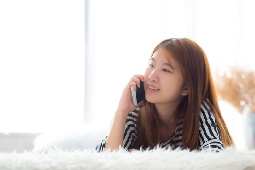 Beautiful young asian woman smiling lying relax on the bed in the morning, girl using mobile smart phone talking enjoy, communication and social network concept.