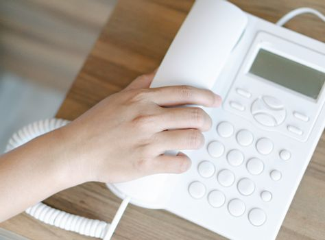 Closeup woman hand holding telephone receiver and dialing a phon