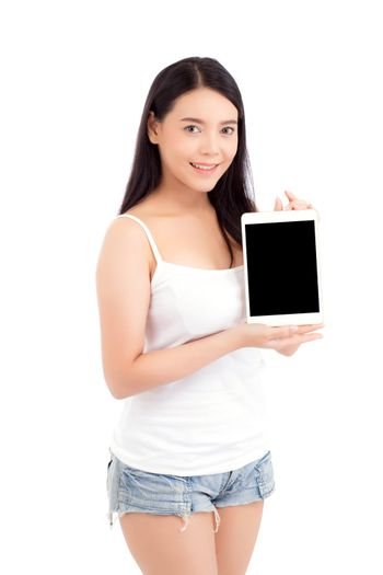 Portrait of asian young woman standing showing blank screen tablet isolated on white background, girl showing technology, business and communication concept.