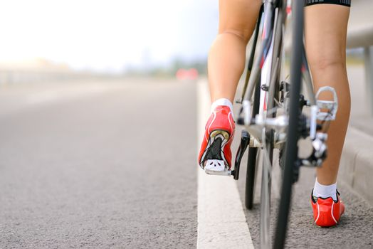Woman Cyclist Preparing for Riding Bike on the Road. Close View of Bicycle and Legs. Adventure, Travel, Healthy Lifestyle and Sport Concept.