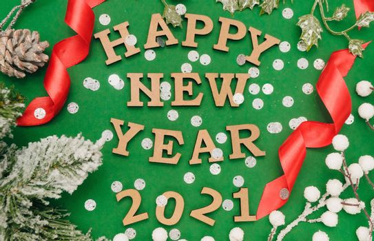 Happy new year 2021.Wooden letters in New Year's cap on green background with red ribbons,silver confetti and spruce branch.Festive decoration or postcard concept.Top view and flatlay.copy space
