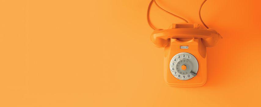 An orange vintage dial telephone.