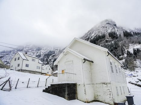 White wooden houses in wintry Norway. Snow and mountains.
