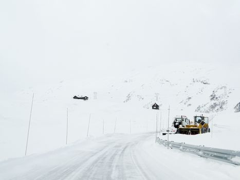 Excavator snow shovel truck on snowy road at work, Norway.
