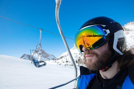 Man skier sitting in ski lift