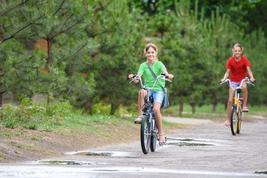 Two girls ride a bike on a rainy warm day
