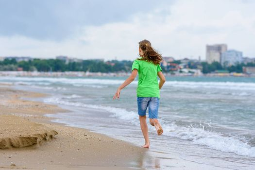 A girl happily runs along the sea coast, view from the back