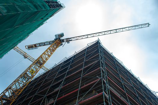 Construction site jib crane. Construction of new modern buildings. Urban architecture