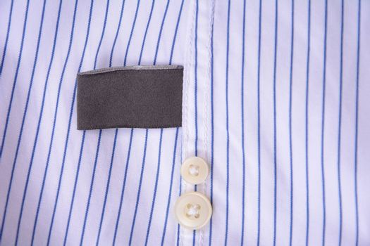 Black blank clothing tag label on shirt fabric texture background