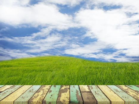 Empty wooden table for displaying products On the background are grass fields and blue sky.