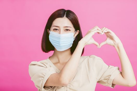young woman wearing medical mask and showing heart shape gesture
