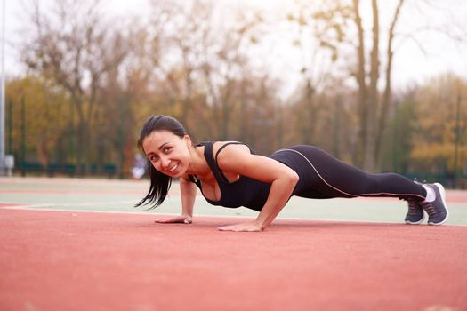 Happy girl doing plank outdoor on playground. Healthy lifestyle. Morning workout positive emotion smiling sportive people. one female training