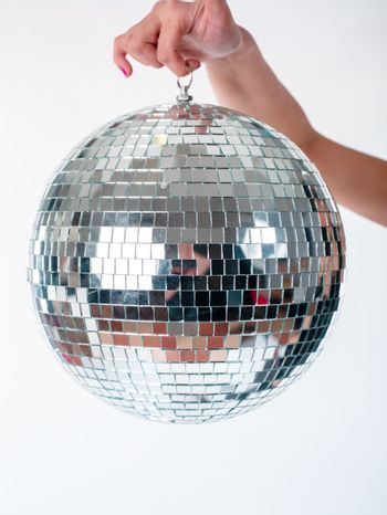 Hand holding Shining Disco Ball dance music event equipment isolated on white background
