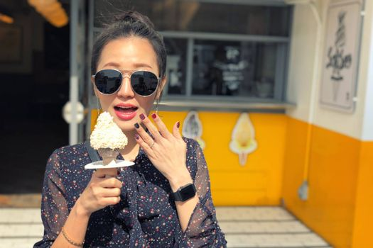Outdoor closeup fashion portrait of young woman with sunglasses eating ice cream in summer hot weather in Seoul, Korea