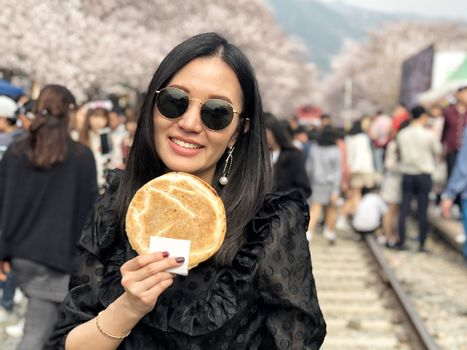 Woman eating Egg bread dessert at Jinhae Gunhangje Festival street food in Seoul, South Korea