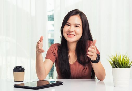 Work from home, Asian business young beautiful woman smiling sitting on desk workspace raise hand explain job communication with team video conferencing on digital tablet computer at home office