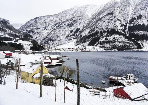 Winter landscape village at fjord lake river in Framfjorden, Norway.