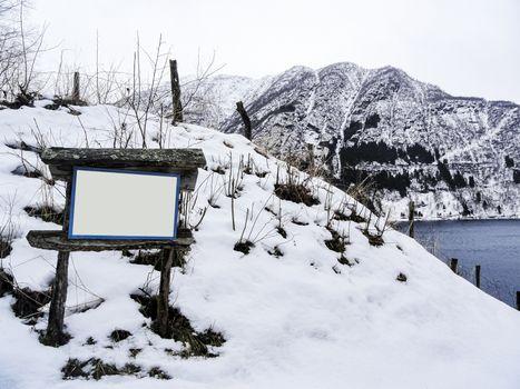 Empty wooden tourist information sign in winter, Norway, Vik Kommune.
