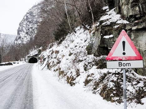 Red road sign Bom and tunnel in Norway. Snowcovered roads.
