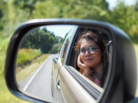 A woman's side-view mirror looking out of the car While driving a car.