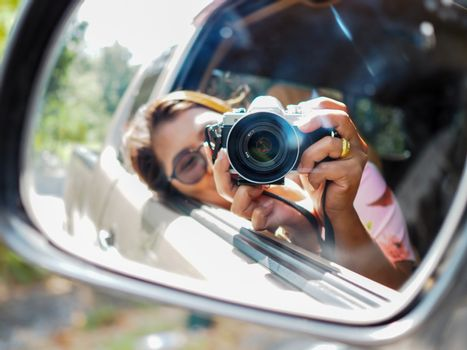 A young woman held a digital camera and took a picture of herself smiling reflected in the car mirror. Focus on camera.