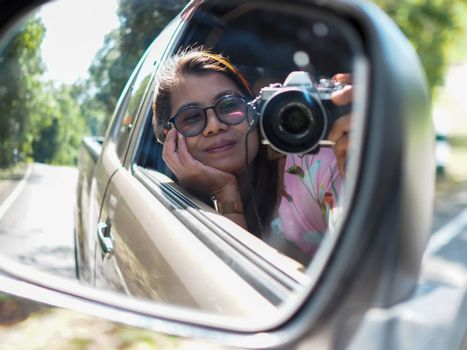 A young woman held a digital camera and took a picture of herself smiling reflected in the car mirror.